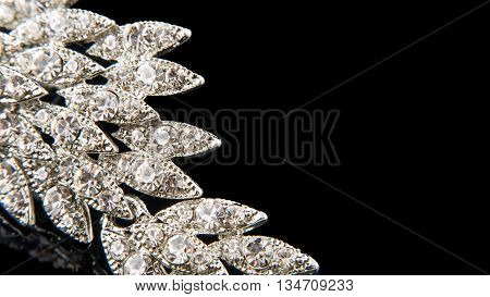 Details of vintage brooch with crystals isolated on black. Empty space for your text