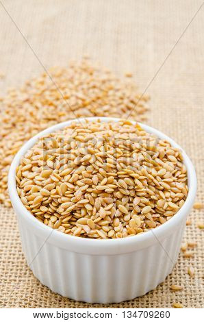 Heap of gold linseed or flax seeds in white cup on sack background concept for healthy nutrition