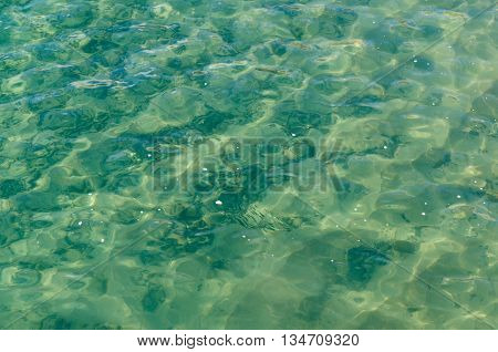 Teal transparent water with wave ripple in sea or ocean. Travel tourism vacation and summer holidays concep