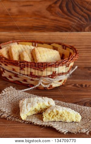 Single square biscuit with sugar on burlap, a bunch of biscuits in wicker basket on brown wooden background. Home baking
