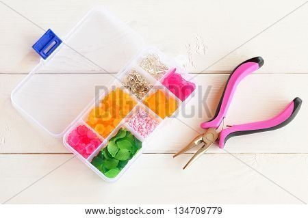 Open organizer with beads, plastic flowers and metal accessories for hand jewelry on white wooden background. Pliers, handy tool. Handicraft concept