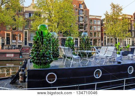 AMSTERDAM, NETHERLANDS - MAY 5, 2013: Trees of empty bottles make this residential barge different from other moored along the canal.