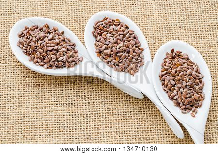 Brown flax seeds or linseed in white spoon on sack background.
