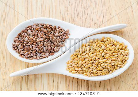 Difference of Golden linseeds and brown linseeds (flax seeds) in white spoon on wooden background.