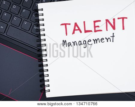 Handwriting Talent Management on notebook with with laptop keyboard (Business concept)