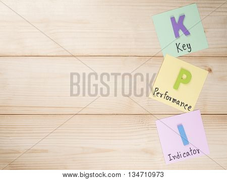 KPI (Key Performance Indicator) on notepaper with wood background (Business concept)