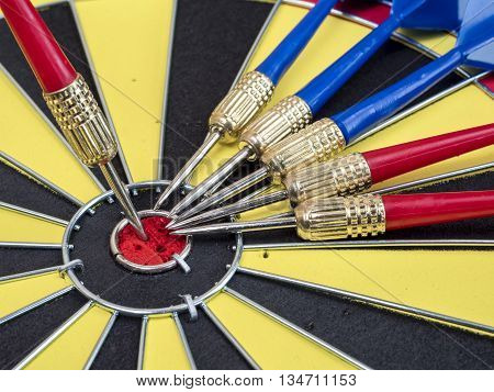 Single dart arrows stand on the center of dart board and many dart arrows on dart board (Leadership Concept)