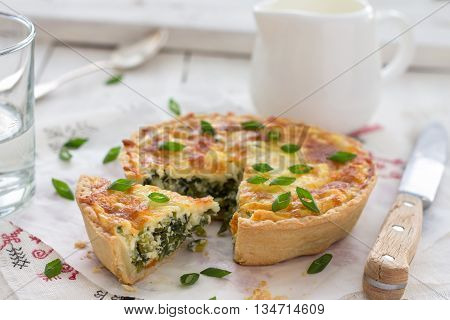 Mini quiche with green onions and cheese on a light wooden background, selective focus