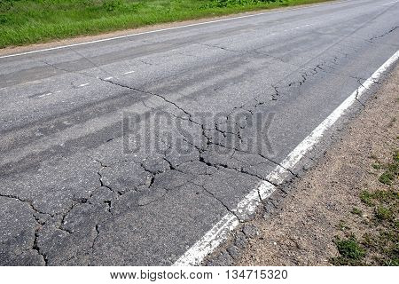 Suburban road in bad condition needs repairs. Rural car road with broken asphalt in sunny summer day diagonal view