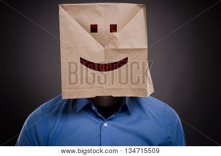 Businessman with a smiling face on a paper bag think positive concept image