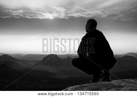 Short Hair Hiker In Shirt Sit On Rock, Enjoy Foggy Scenery