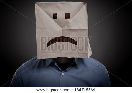 Businessman with an unhappy face on a paper bag negative concept image