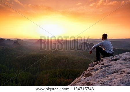 Adult In Black Trousers, Jacket Sit On Cliff's Edge