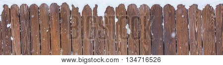 Rural winter scene. Snow covered wooden fence, brown planks panoramic background