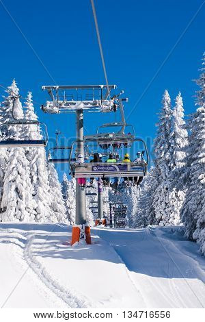 Kopaonik, Serbia - January 19, 2016: Vibrant photo of ski resort Kopaonik Serbia, people on the ski lift ,skiers on the piste among white snow pine trees, blue sky