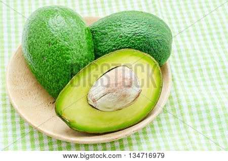 A sliced avocado in wooden dish on tablecloth.