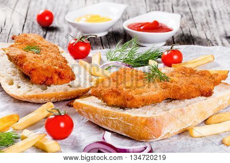 sandwich with ciabatta and Bread Crumb Coated fried pork chop with french fries red onion cherry tomatoes and dill on a parchment paper studio lights view from above close-up