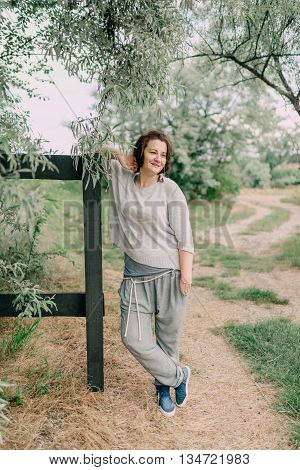 Camping under the trees at the wooden fence posing woman in pants