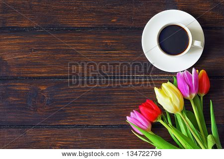cup of coffee and bouquet of tulips on a dark wooden table