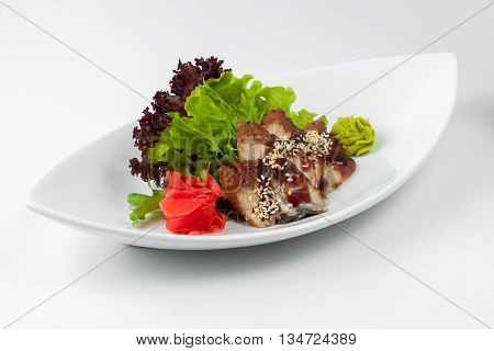 A dish of smoked eel with herbs wasabi sesame and ginger