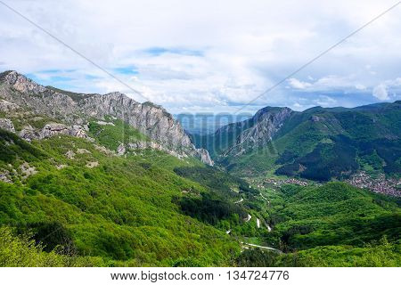 The picture is taken in Vratsa mountain national park (Bulgaria) on the path to Ledenika cave. In the photo you can see on the left West ridge of Vratzata passage and part of the village Zgorigrad.