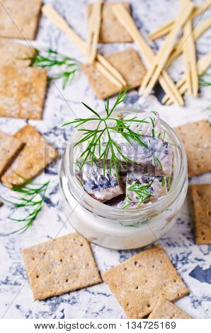 Slices of marinated herring with cream and dill. Selective focus.