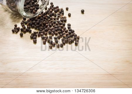 Black pepper spilled out on wooden background with copyspace