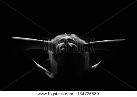 female silhouette with closed eyes in dark monochrome image