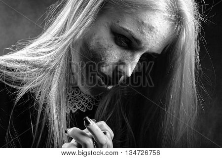 sad pensive girl with smeared cosmetics on pimply skin on black background monochrome