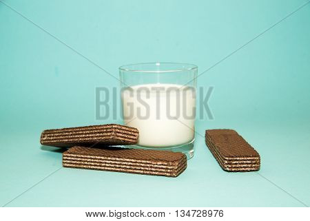 A glass of milk and waffles on a blue