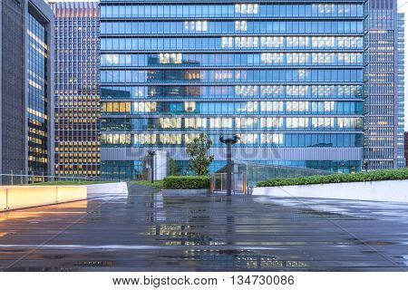 wood wet floor front modern office building at twilight in tokyo