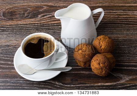 Coffee, Jug Milk And Three Muffins On Wooden Table