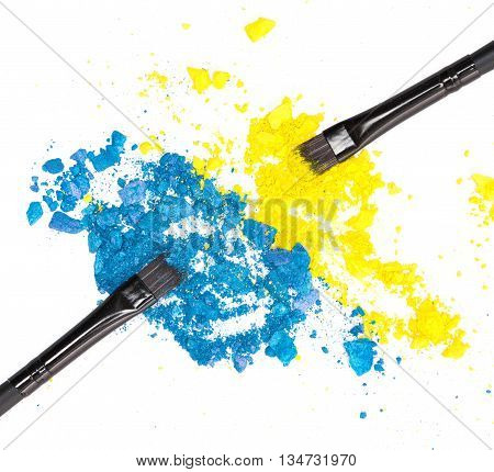 Close-up of makeup brushes with crushed compact blue and yellow eyeshadow on white background. Modern stylish eye makeup