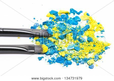 Close-up of makeup brushes with mixed crushed compact blue and yellow eyeshadow on white background. Modern stylish eye makeup. Focus on the front brush