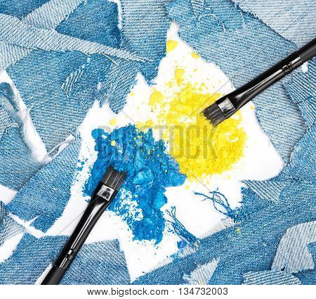 Close-up of makeup brushes with crushed compact blue and yellow eyeshadow surrounded by rags of denim. Modern stylish eye makeup
