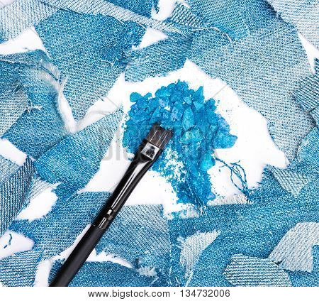 Close-up of makeup brush with crushed compact blue eyeshadow surrounded by rags of denim. Modern stylish eye makeup