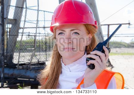 Beautiful woman engineer in the oil field talking on the radio wearing red helmet and work clothes. Pump jack background. Oil and gas concept.