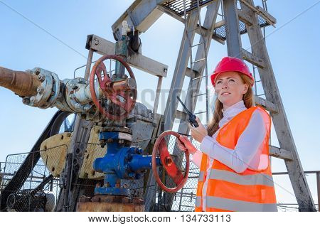 Beautiful woman engineer near well head valve in the oil field talking on the radio wearing red helmet and work clothes. Pump jack background. Oil and gas concept.