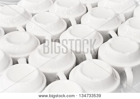 Rows of clean white upside down cups in a cafeteria or restaurant ready to serve a hot beverage full frame background