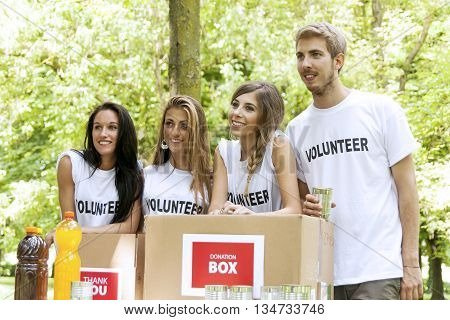 group of teenagers volunteering receives gifts in the park