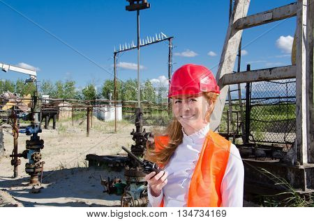 Beautiful woman engineer near well head in the oil field talking on the radio wearing red helmet and work clothes. Pump jack and pipeline background. Oil and gas concept.