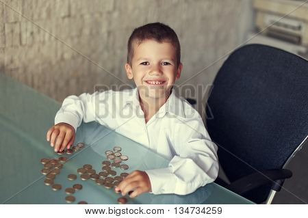 Happy little businessman at glass desk with coins in office
