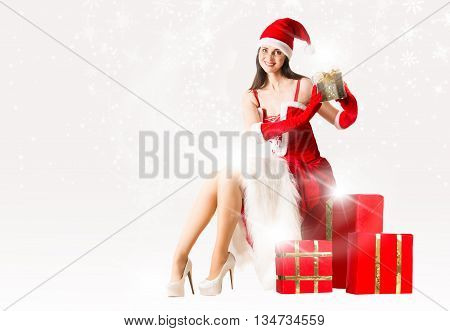 Attractive woman in Santa Clause outfit sitting on the present box and holding Christmas present. Christmas background