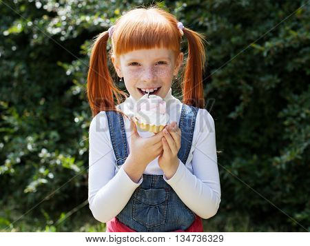 The little red-haired girl with freckles eating cake with cream