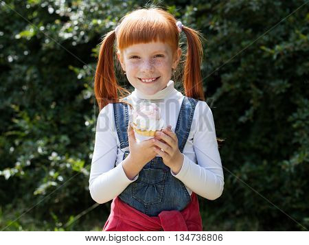 The little red-haired girl with freckles holds a cake with cream and smiles broadly