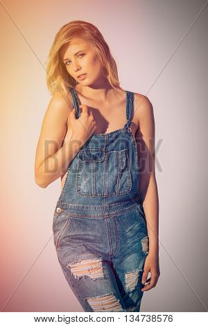 Sensual beauty. Studio shot of beautiful young woman in jeans overall looking at camera