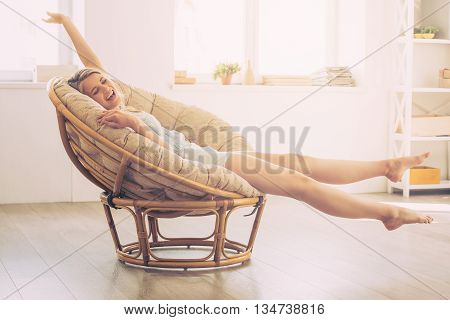 Enjoying carefree time at home. Cheerful young woman keeping eyes closed and stretching out hands while sitting in big comfortable chair at home