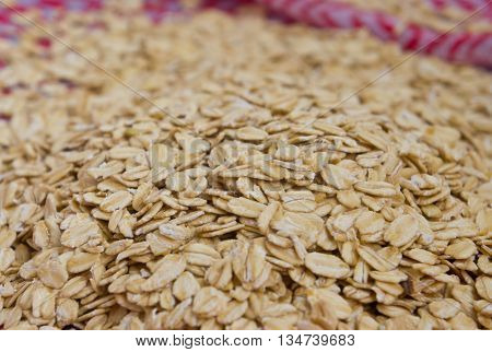 porridge crude lies on a cloth, flakes of porridge are scattered, fabric of white and red color,