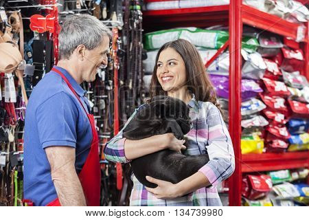 Salesman Looking At Customer With Bulldog In Pet Store
