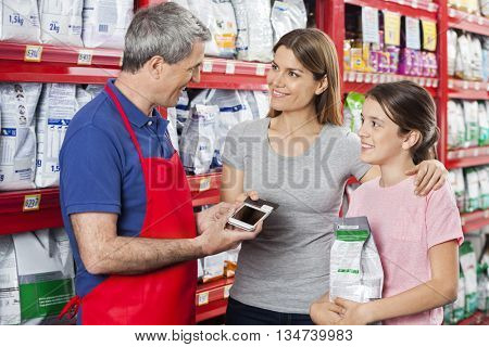 Salesman Accepting Payment From Family In Pet Store